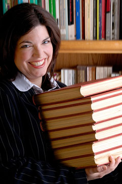 a smiling library assistant with a stack of books