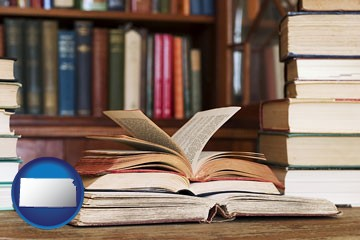 books on a library table and on library bookshelves - with Kansas icon