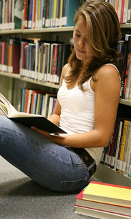 young woman reading a book in a library aisle